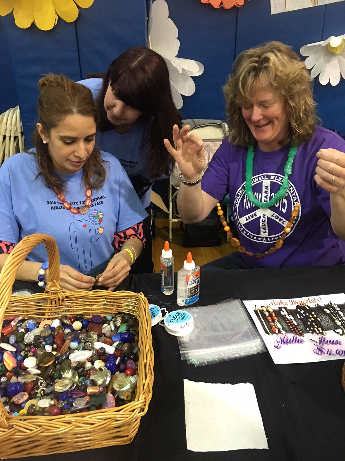 Fair volunteers doing crafts with young children
