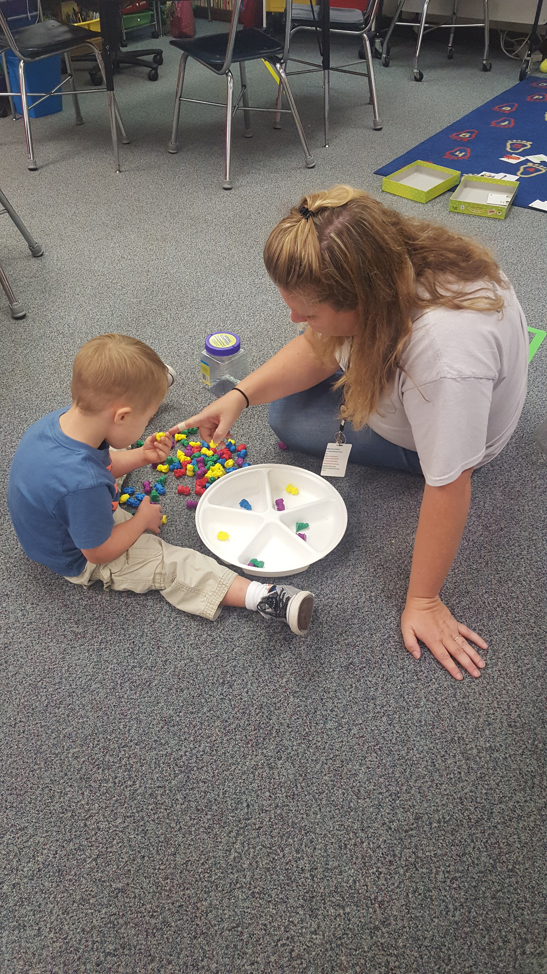 Dana Buie, on the floor instructing a student using manipulatives