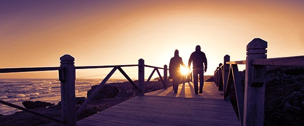 Two people walking on dock at sunset.