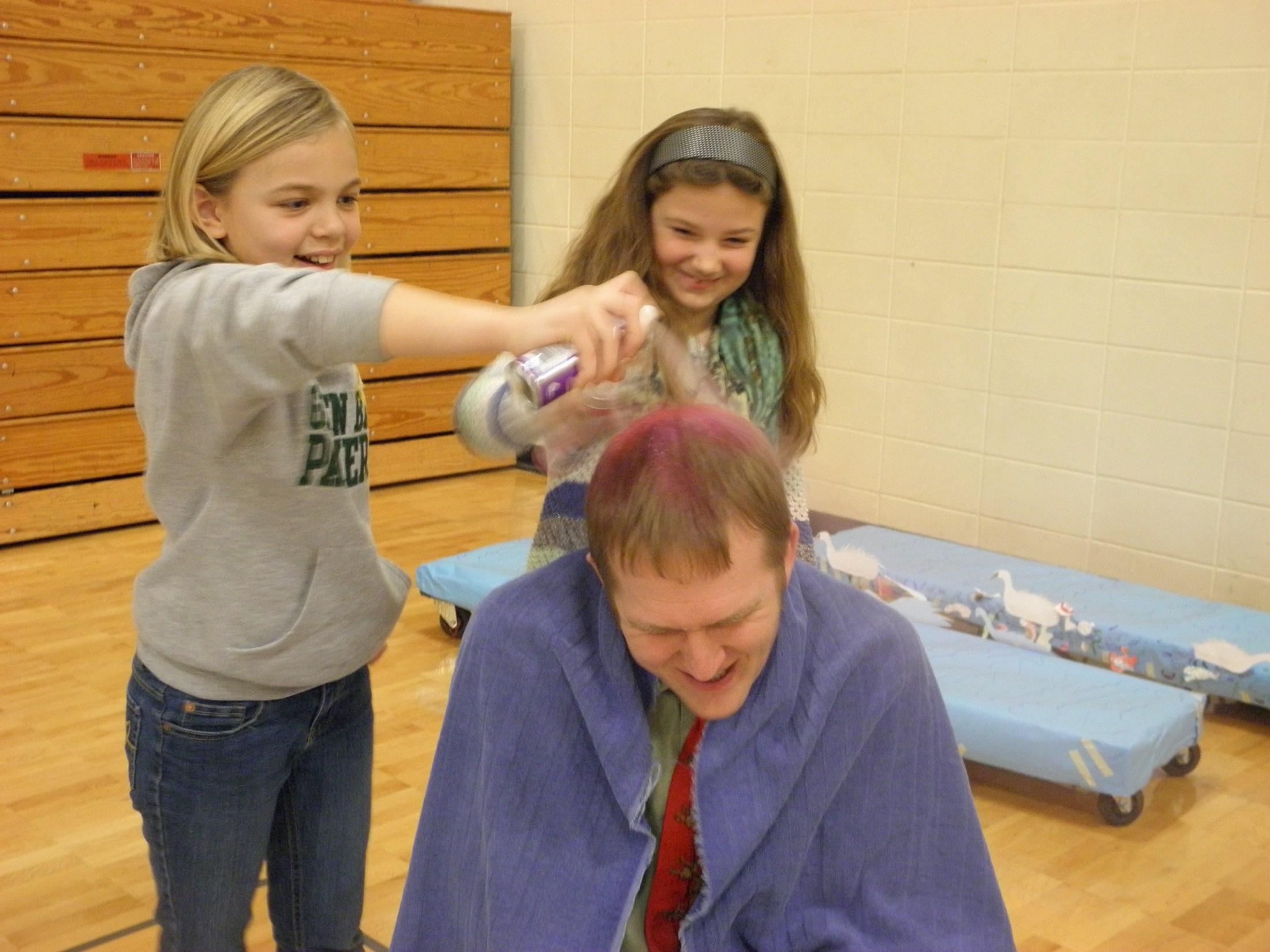 Students spray painting teacher's hair.