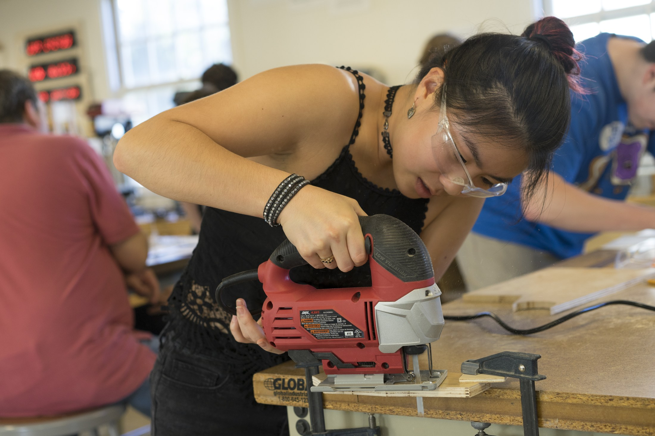 student cutting wood in engineering class