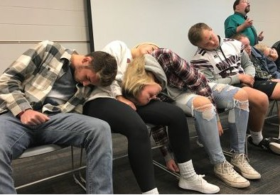 4 students asleep on folding chairs during hypnosis