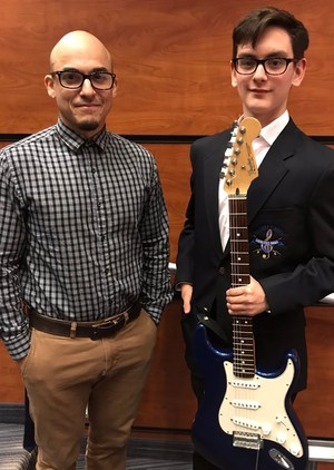 picture of assistant band director and Trenton Garcia holding a guitar