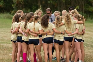 Otsego girls huddle together in a circle before the cross country meet.
