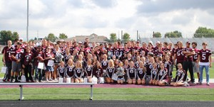 football team and cheerleaders in maroon uniforms on football field pose for pic