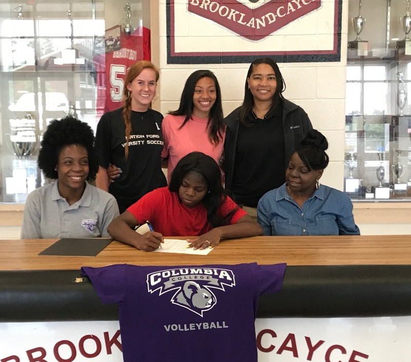 Diamond Moore, seated center, is flanked by Columbia College volleyball coach Keyaira Stevenson, seated left, mother Carol Hyman, seated right, as some fellow Brookland-Cayce High volleyball players look on. She signed a letter of intent Thursday.