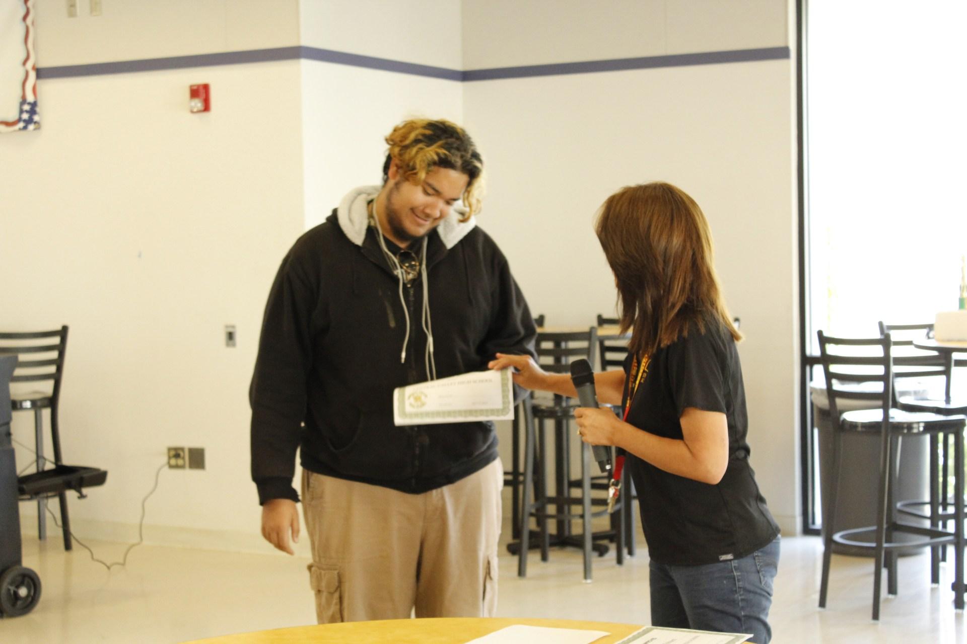 Sam Romo receiving an Award from Mrs. G