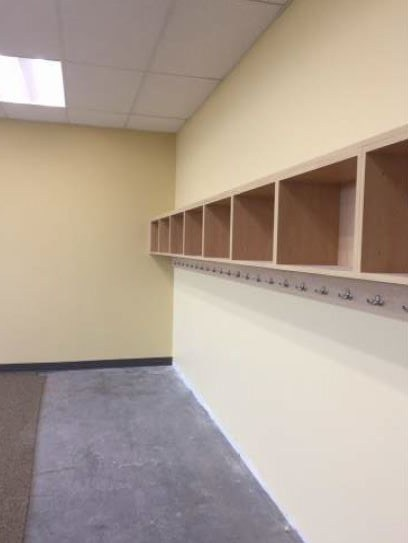 A row of wall-mounted locker cabinets with hooks on a yellow classroom wall