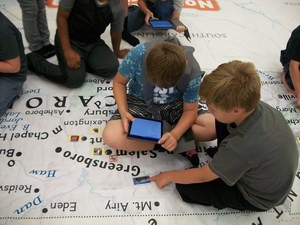 Two boys are using an iPad to look for information about a place on the North Carolina map.