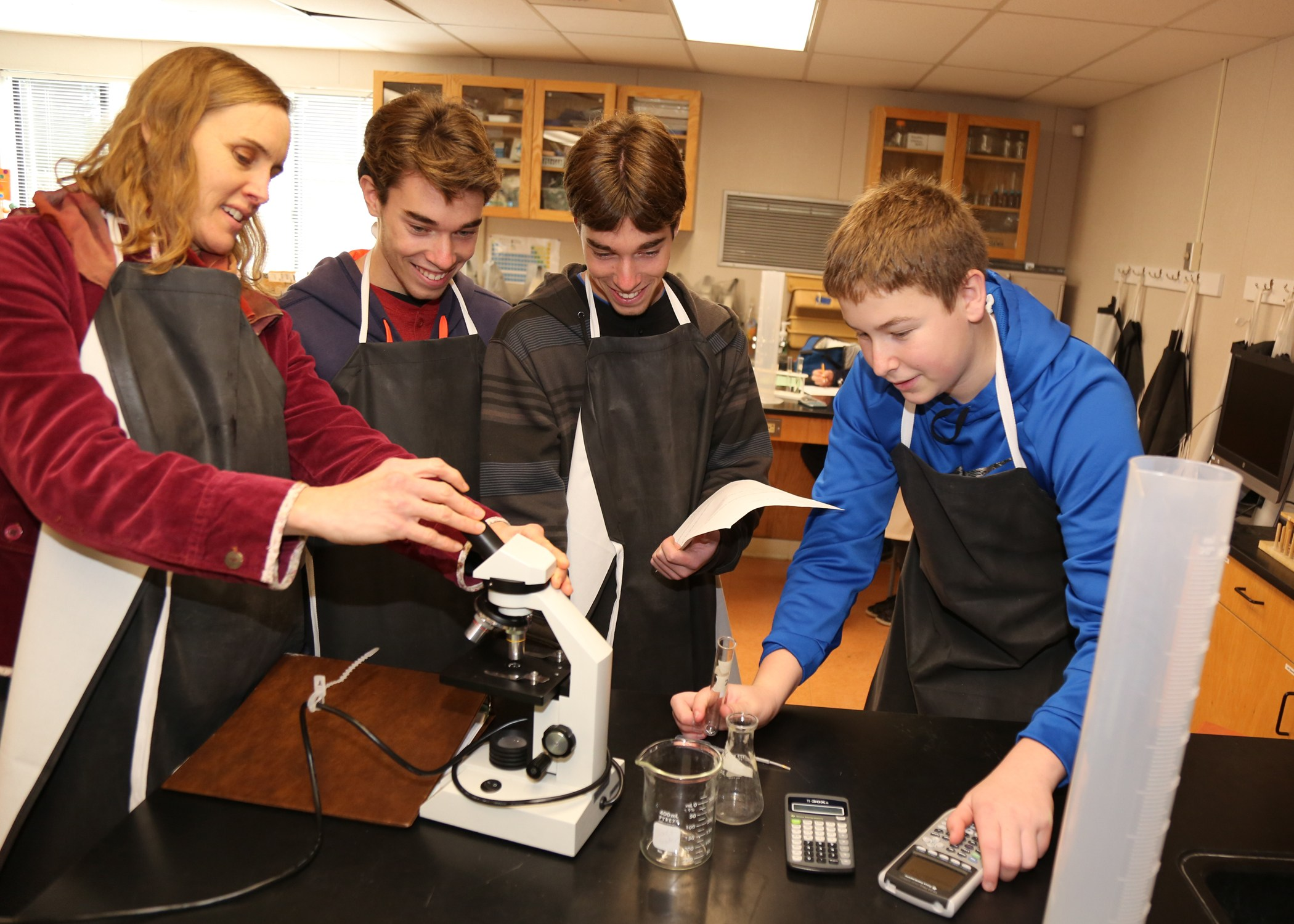 Chemistry teacher with 4 students at microscope