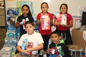 5 students holding household items purchased for the hurricane relief donation project.