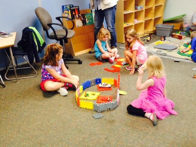 Girls playing with waffle blocks.