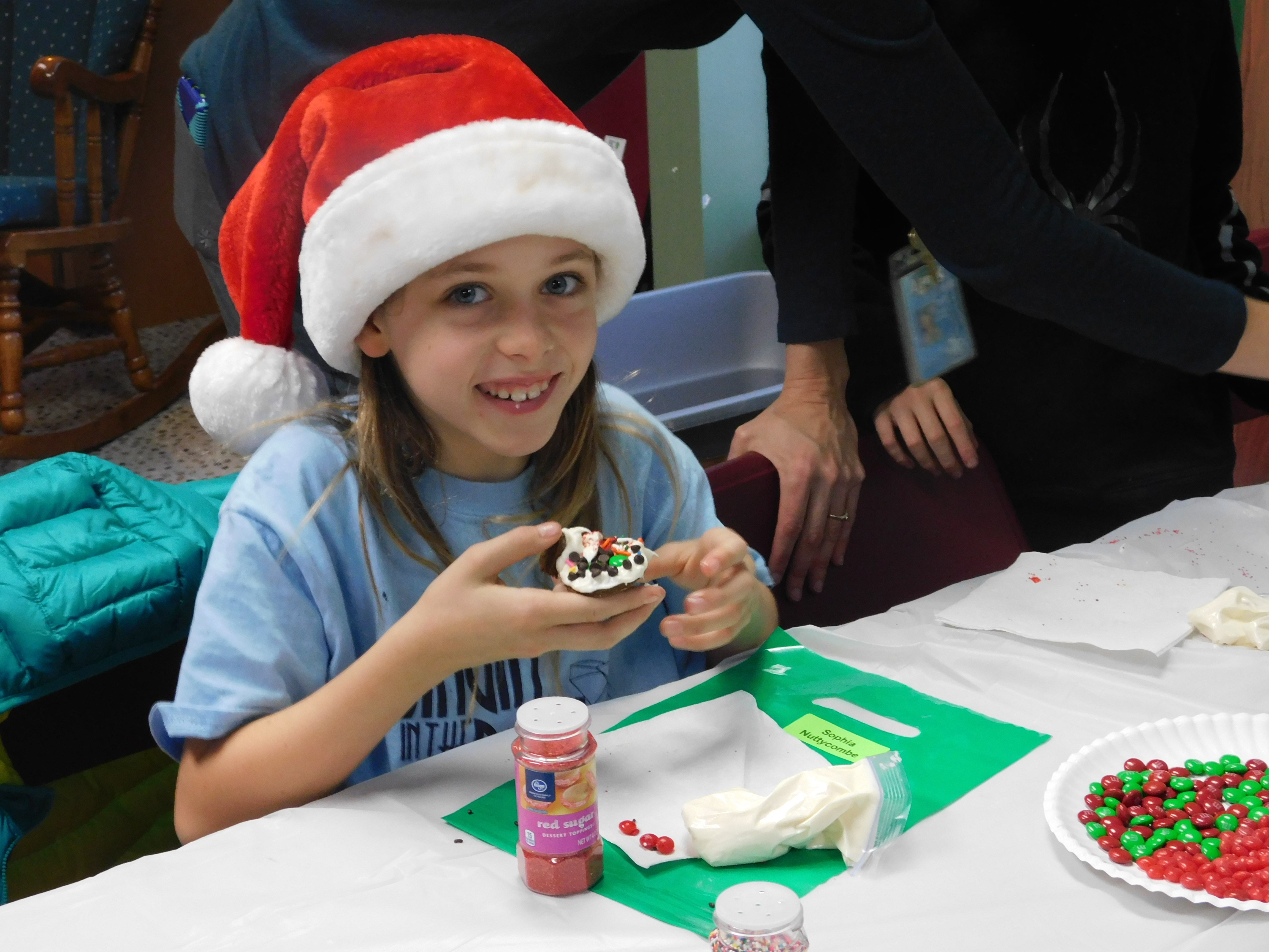 Student eating a cookie at the Holiday Party.