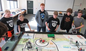 TKMS students practice with their Lego robot to complete missions.