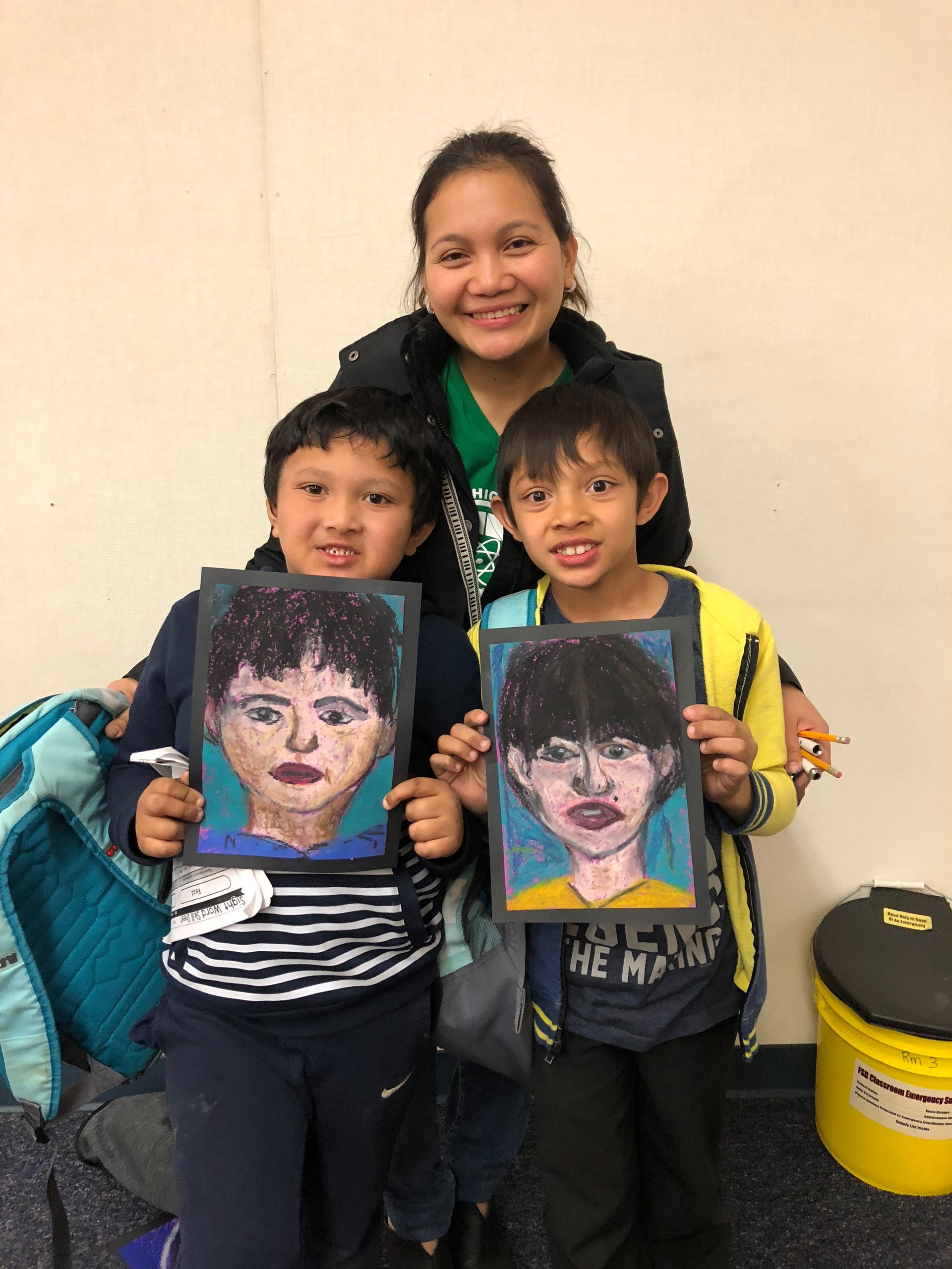 A mom .and her two sons showing their oil pastel portraits