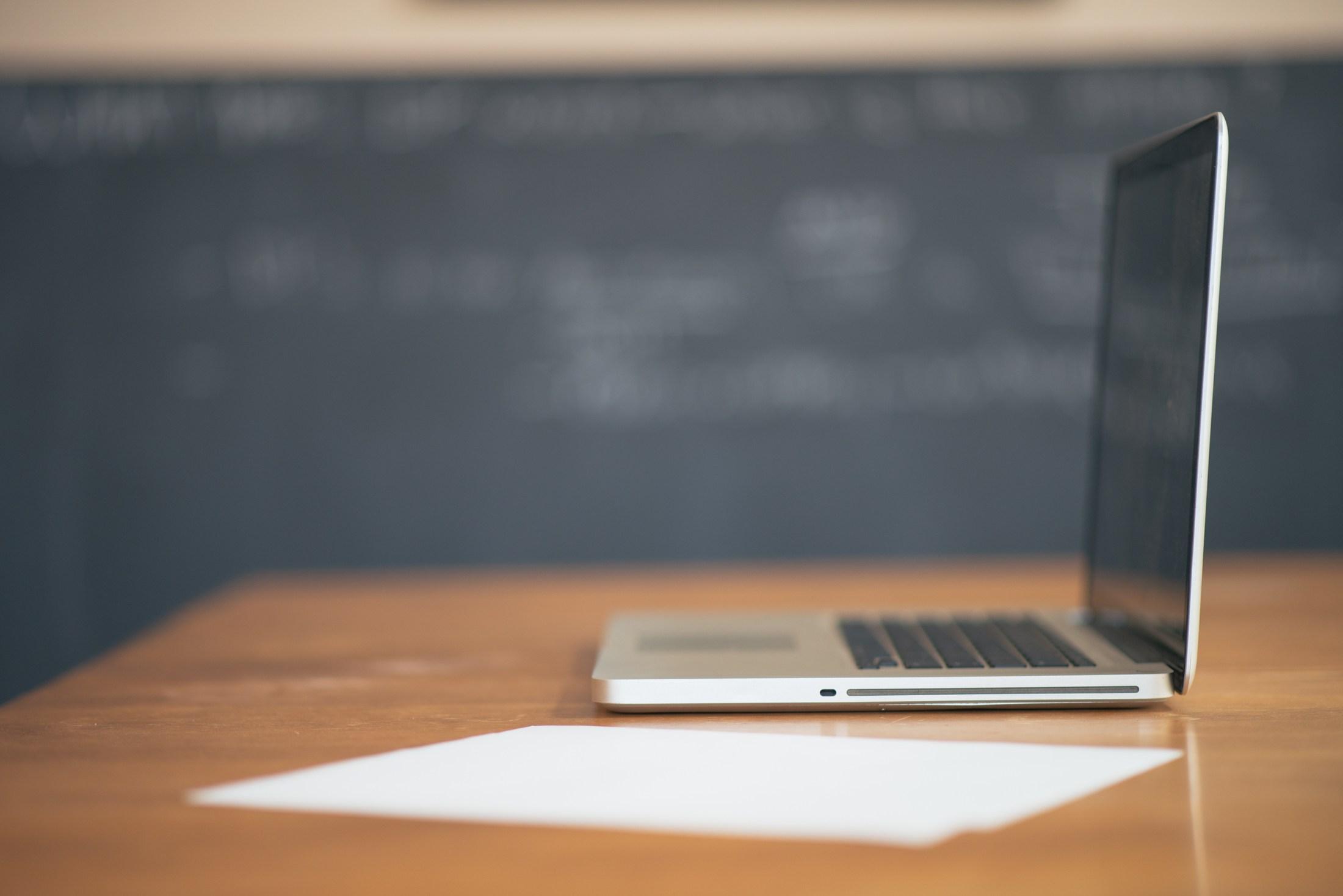 laptop open on a desk in front of chalkboard