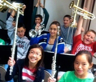 Music students holding their instruments in the air.