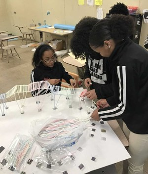 A photo of Baker High School Students constructing a roller coaster out of straws