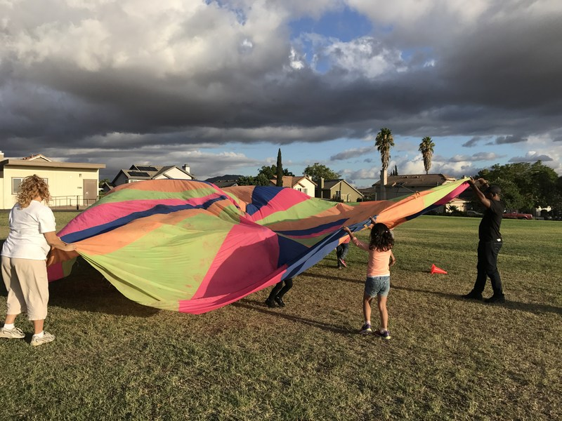 Families playing with parachute