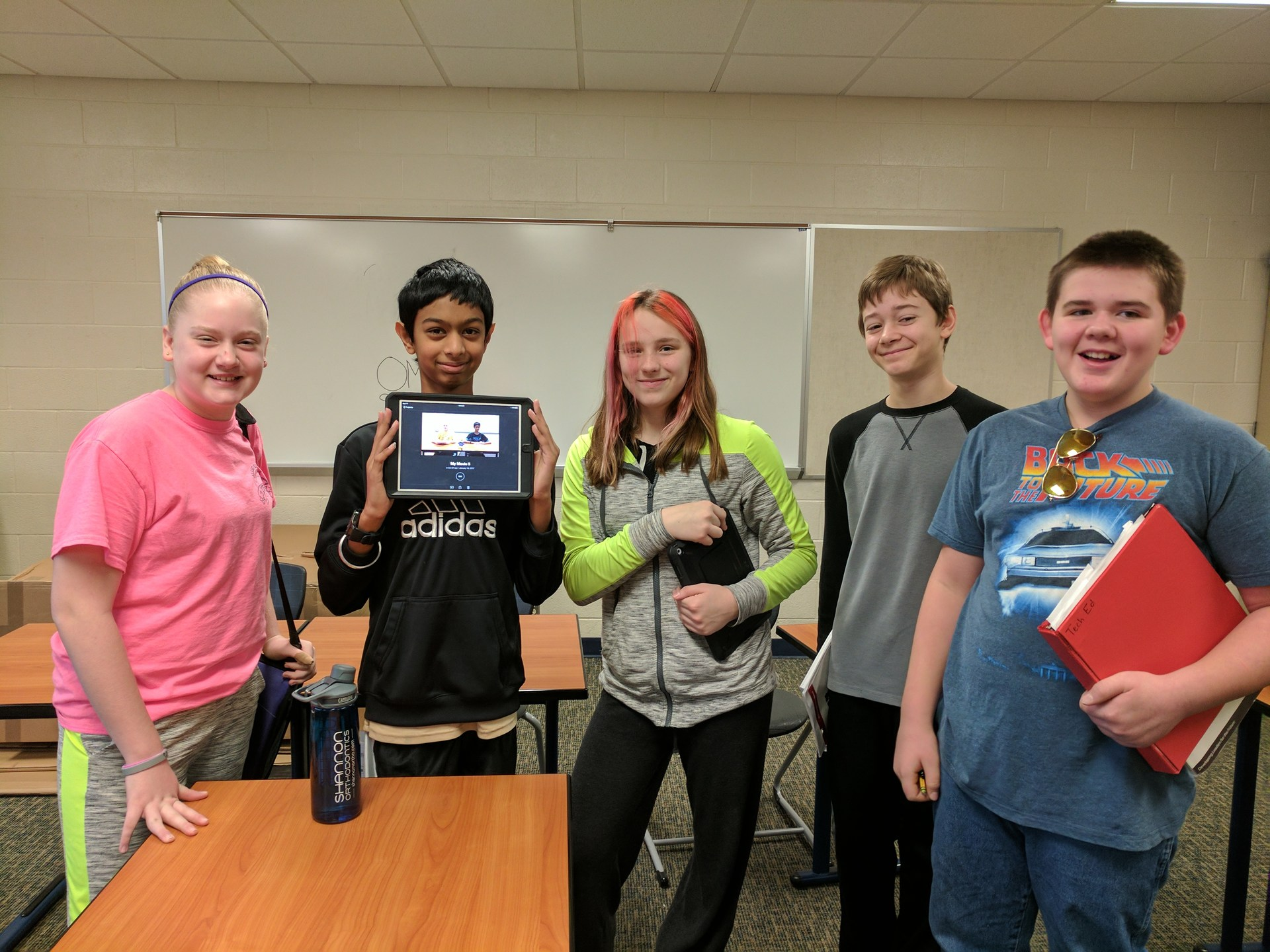 These students hold up an iPad that they used to create the OMS Student News newscast.