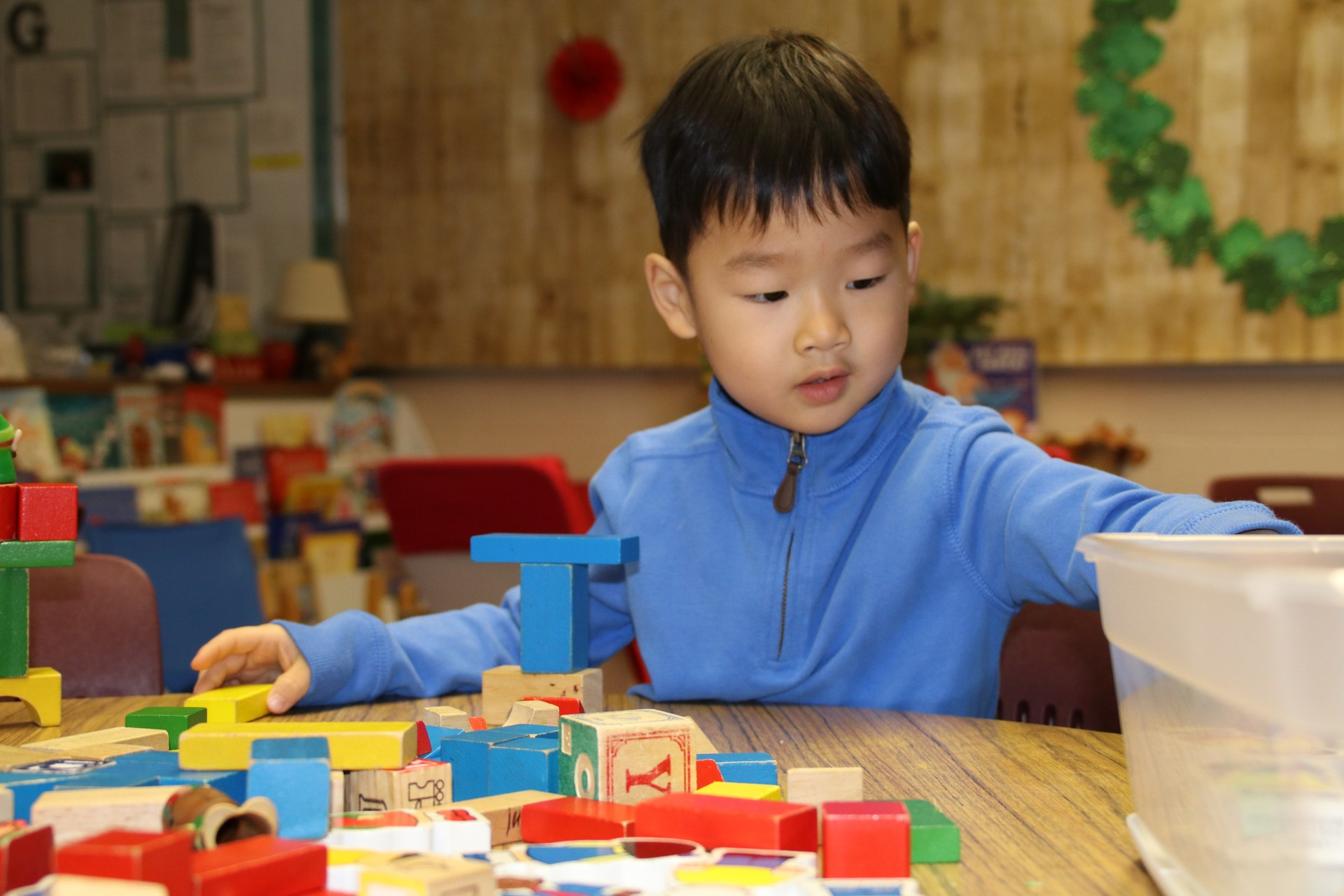 preschool boy in blue shirt playing with blocks at table