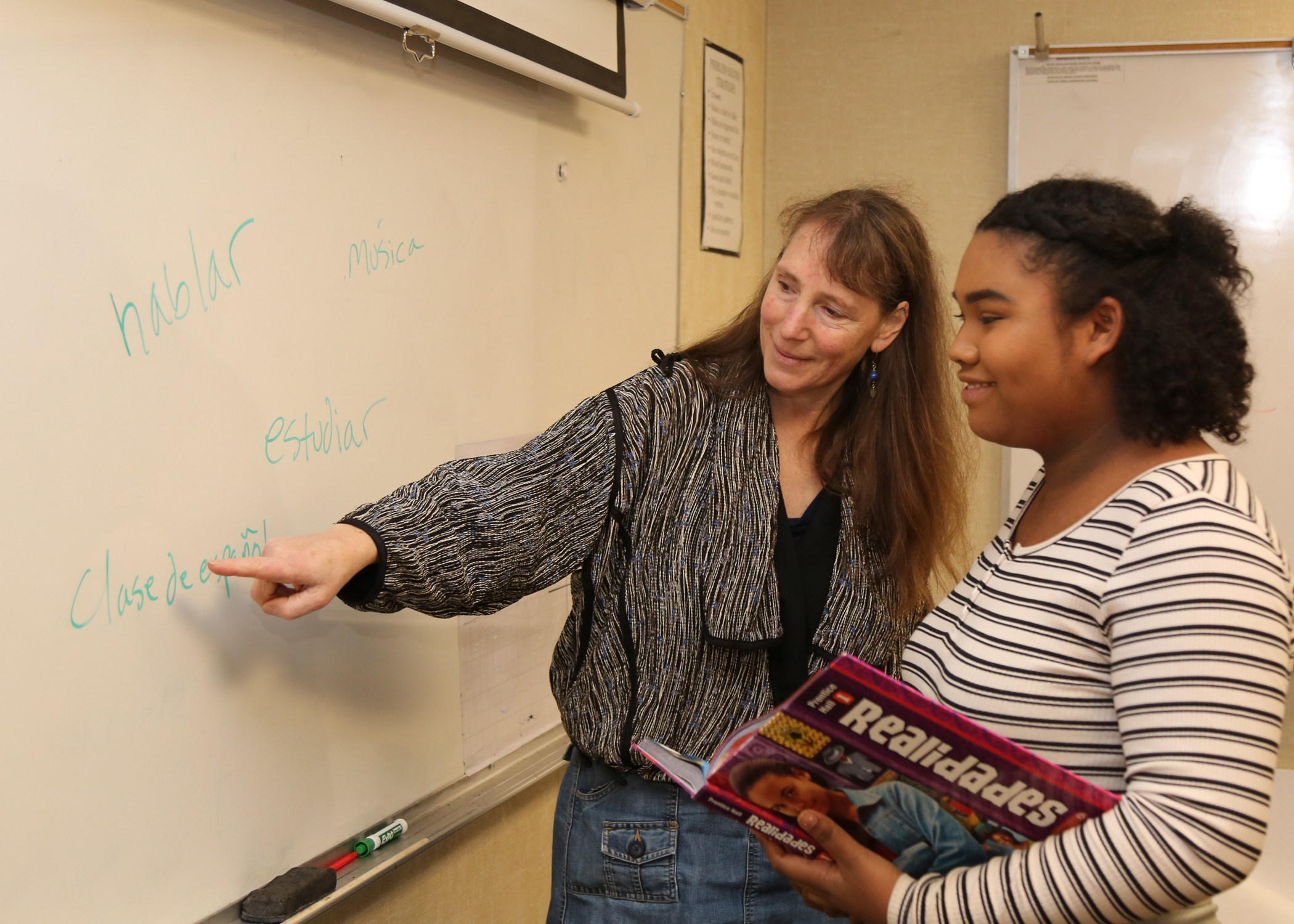 Spanish teacher with student at whiteboard