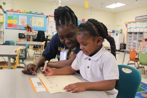 Pre-K Student Writing with the help of the classroom teacher