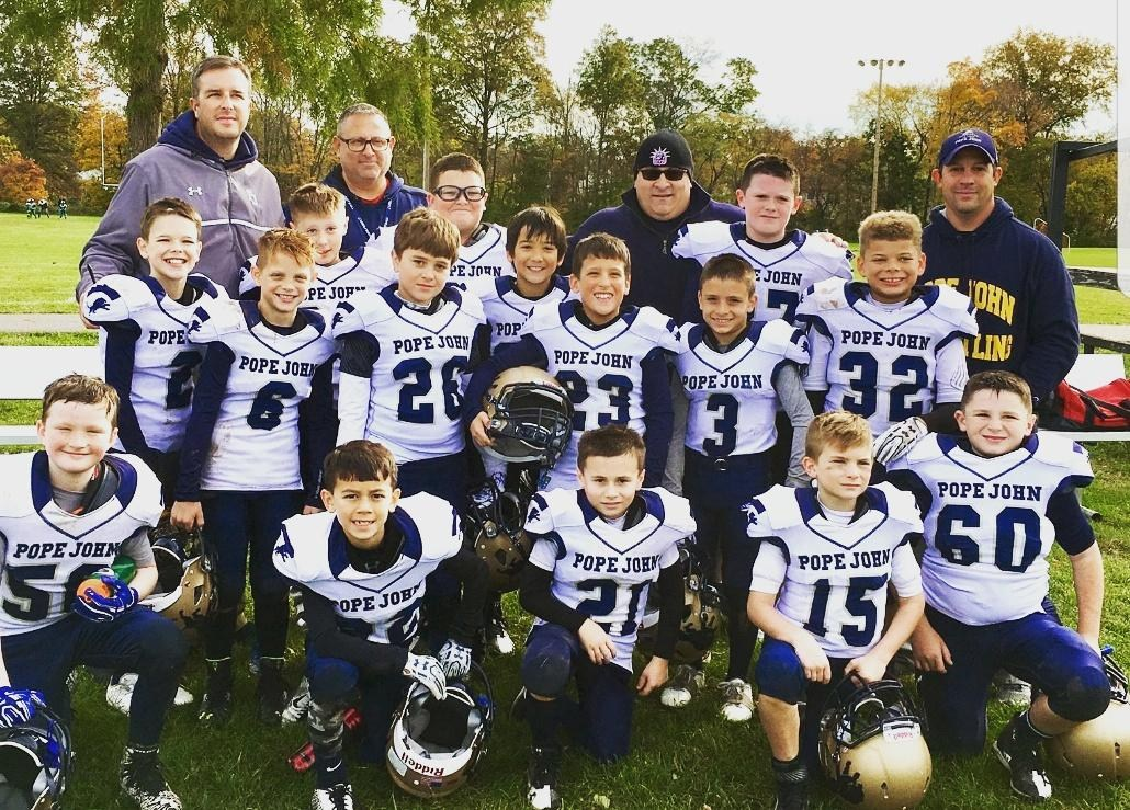 Jr Lions 3rd/4th grade football team pose in white jerseys