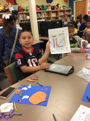 Student showing his coloring sheet for camera.