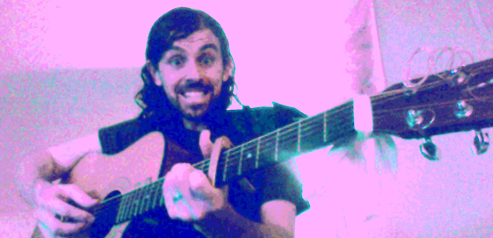 Mr See in a stylized pink and green image, playing his guitar and smiling large