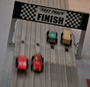 Four cars cross the finish line in one of the final heats of Walnut Elementary School's Pinewood Derby. In lane three is the sassy cat car designed by contest winner Ariana Ramirez, edged in this heat by the sleek racecar designed by second-place winner Andrea Salazar. An unpainted car created by third-place winner Leslie Hernandez trails in on lane one.