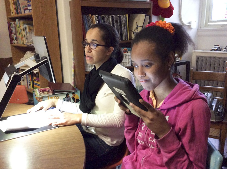 Two female student using technology: ipad and cctv reader