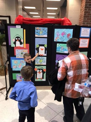 student pointing to their artwork on display for others to see