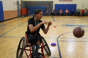 Students play wheelchair basketball.