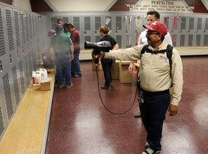 custodian using a backpack disinfection unit in a training situation