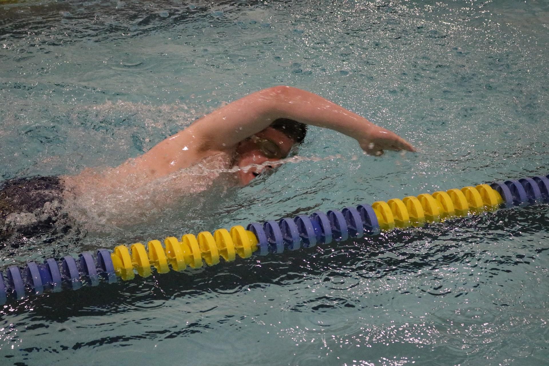 Senior Caleb swimming in his meet.