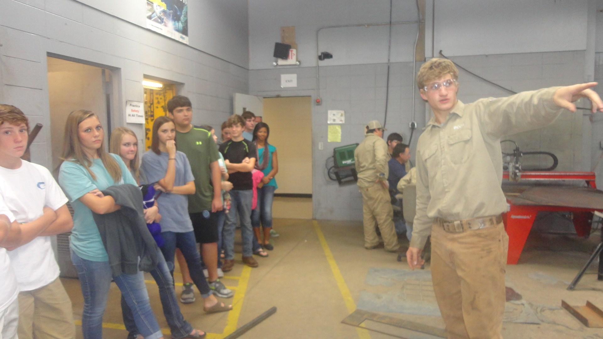 Welding students speaking with 8th graders.