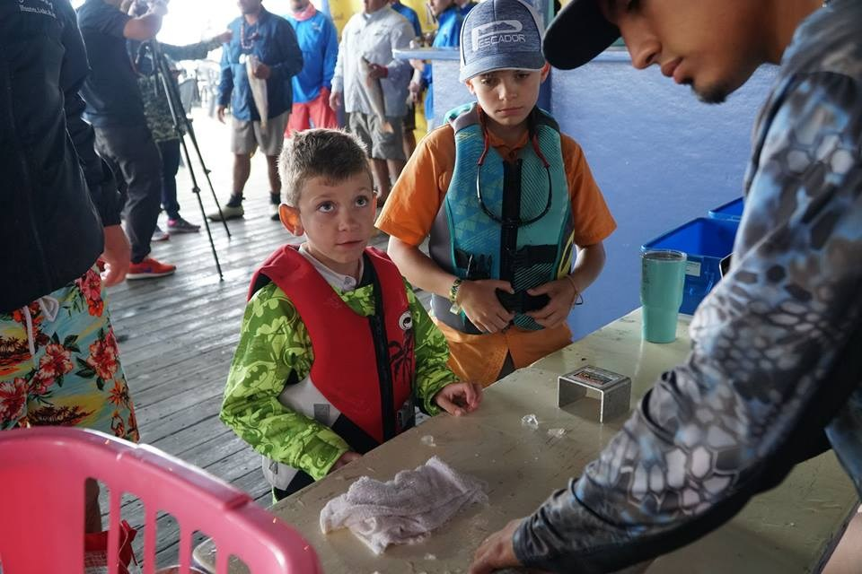 Kid weighing in fish