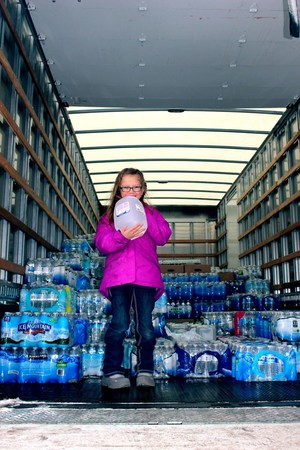 McFall first grader Scarlette Liesenfelder  holds up a jug of water collected for Flint after she organized a water drive at her school.