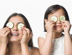 Picture of mother and daughter putting cucumbers on their eyes.