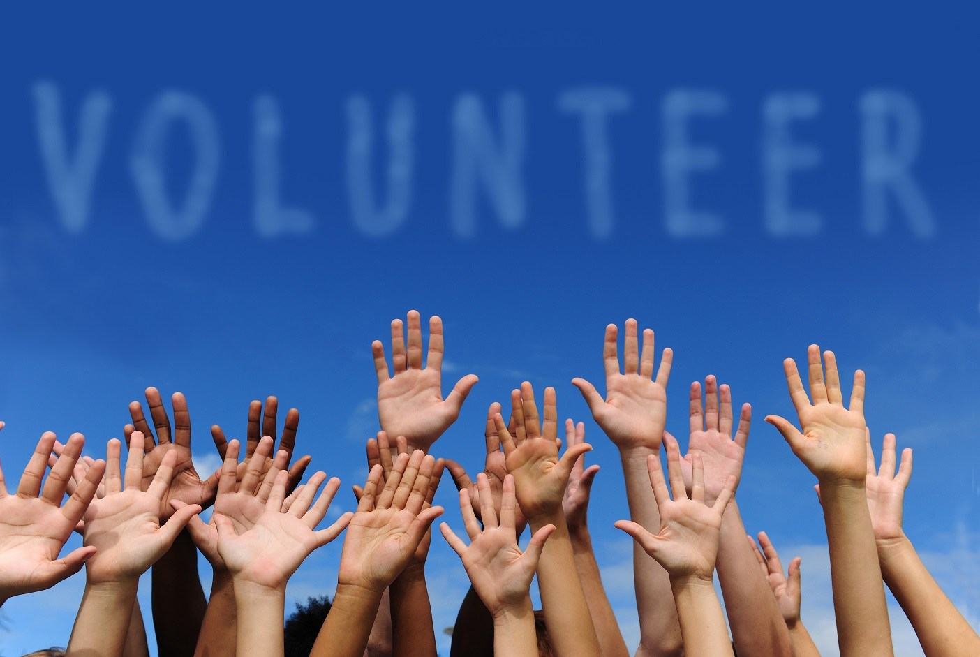 Image of hands raised with word volunteer above them