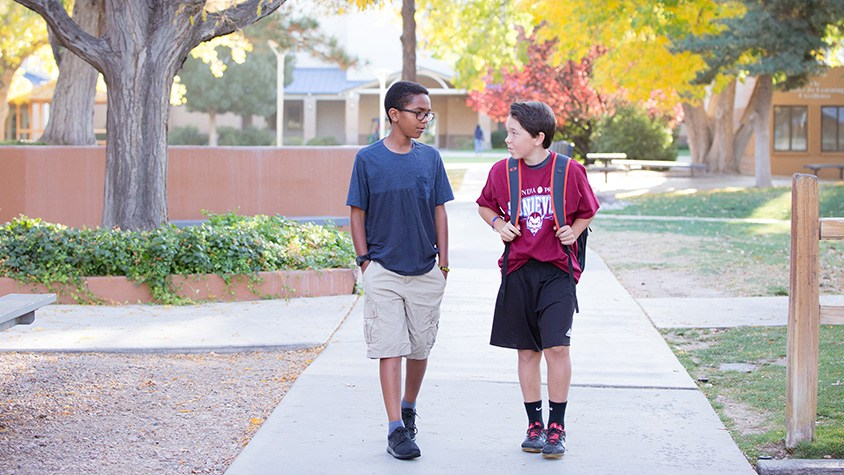 Two middle school boys talk and walk on sidewalk on campus