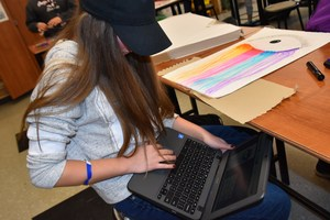 A girl using a Chromebook as a resource to help with her art project.