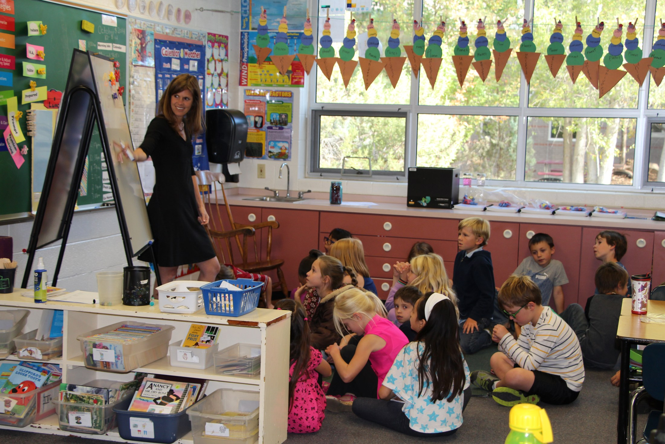 Teacher and students in first grade classroom.