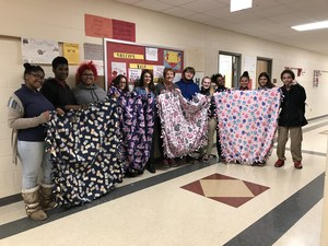 students holding fleece blankets they have made