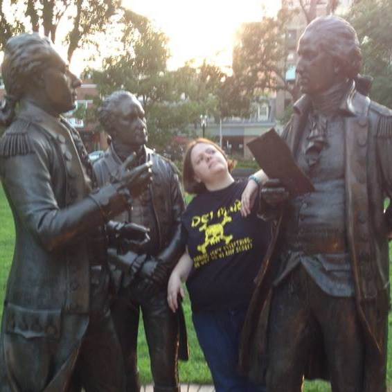 Image of Ms Davison with statues