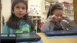 Young girls listening to a story using their iPads