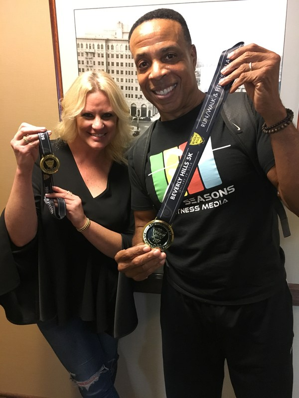 Photo of Jeannine R. and Dion J. showcasing the medals.