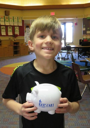 A McFall kindergarten student loves his new piggy bank after learning about saving money.