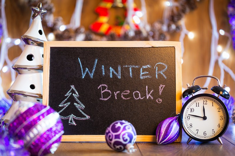 Child's slate with text Winter Break surrounded by Christmas tree decorations and alarm clock